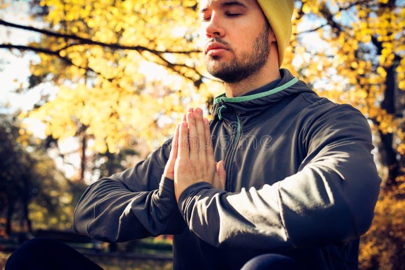 Meditación del hombre joven en naturaleza Ojos cerrados imagenes de archivo