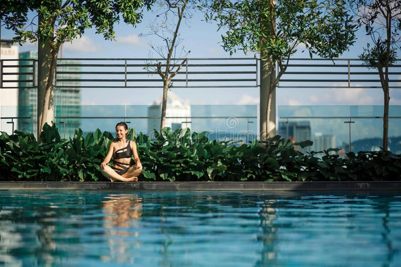 Meditación morena caucásica delgada atractiva entre los arbustos y los árboles verdes en el borde de la piscina en tejado con  fotografía de archivo