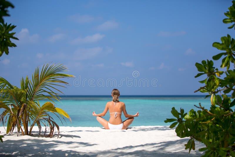 Meditación practicante de la yoga de la mujer joven en la playa que hace frente al océano cerca de una palmera en Maldivas foto de archivo libre de regalías