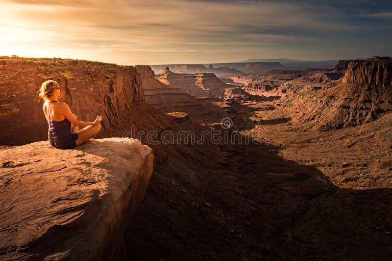Meditación practicante de la yoga de la mujer en la salida del sol Canyonlan hermoso fotos de archivo