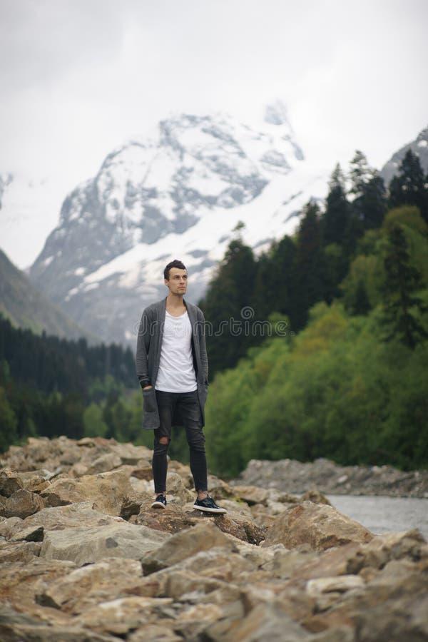 Meditación relajante del hombre del viajero con la forma de vida serena del viaje del paisaje de las montañas y del lago de la vi imagen de archivo
