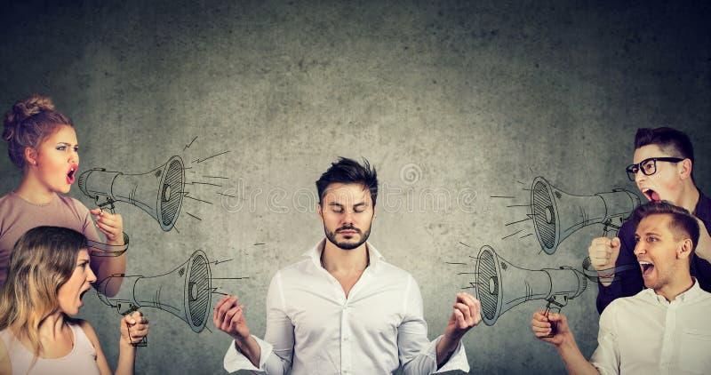 Meditando al hombre de negocios que no presta ninguna atención a la muchedumbre de gritar a gente enojada imagen de archivo