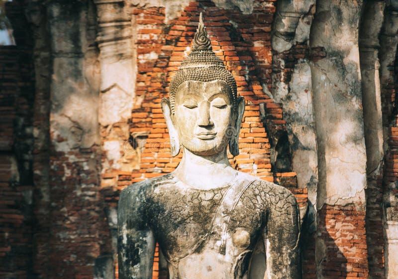 Meditando il ritratto della scultura di Buddha nei raggi luminosi medi del sole di giorno su vecchi precedenti del muro di matton fotografia stock