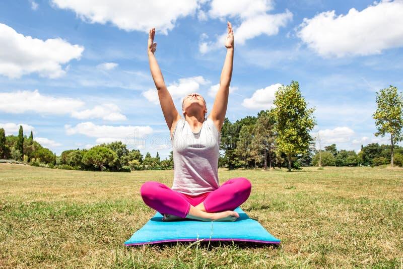 Meditando a jovem mulher que faz a ioga com braços esticados imagens de stock royalty free