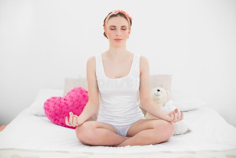 Meditando a jovem mulher que senta-se em sua cama foto de stock