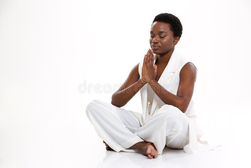 Meditando a la mujer joven afroamericana bonita que se sienta en yoga presente fotos de archivo