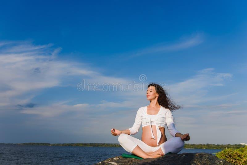 Meditando a mulher gravida fora imagens de stock