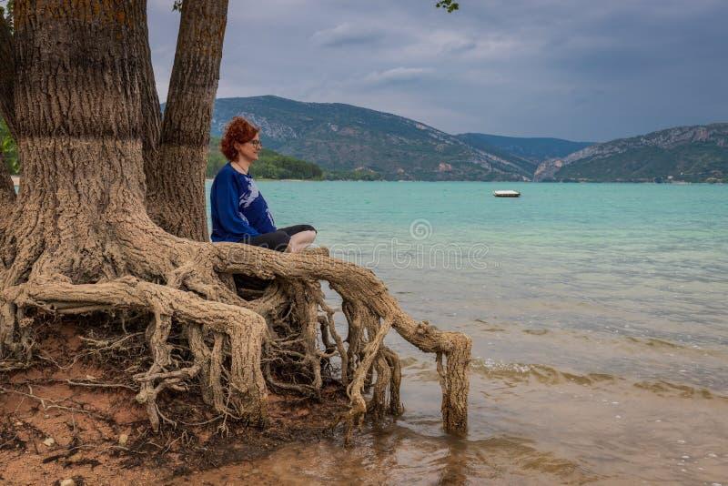 Meditando a mulher que senta-se em uma árvore na costa de um lago imagens de stock royalty free