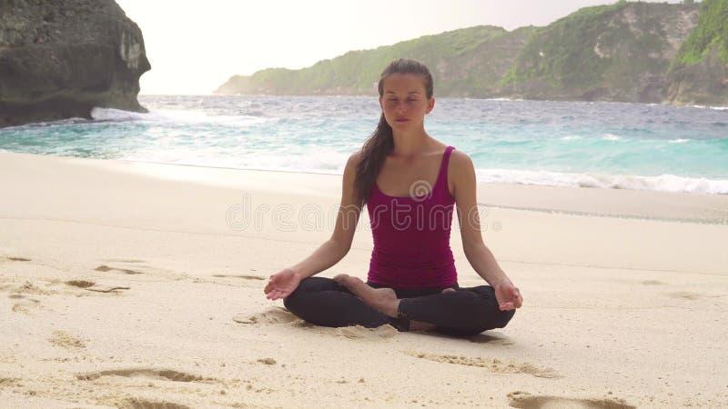 Meditando na posição de lótus, fazendo a ioga exercita na manhã na praia imagens de stock royalty free