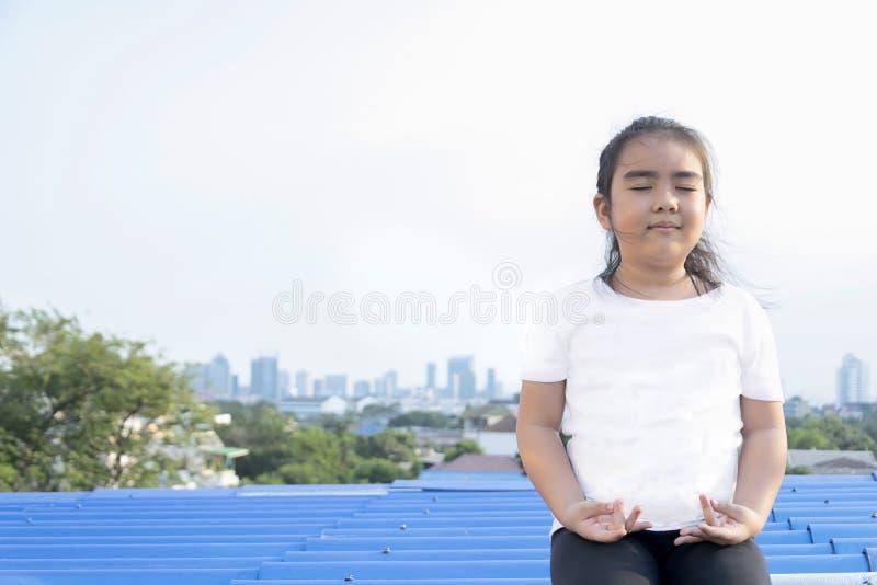 Meditar as mãos da ioga que sentam-se na telhado-plataforma foto de stock royalty free