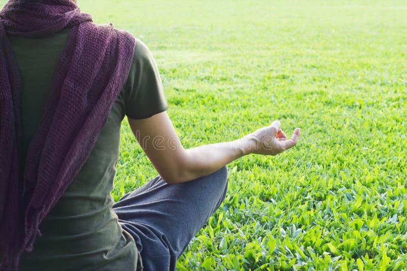 Meditar da mulher da ioga exterior no parque no fundo do campo de grama fotografia de stock