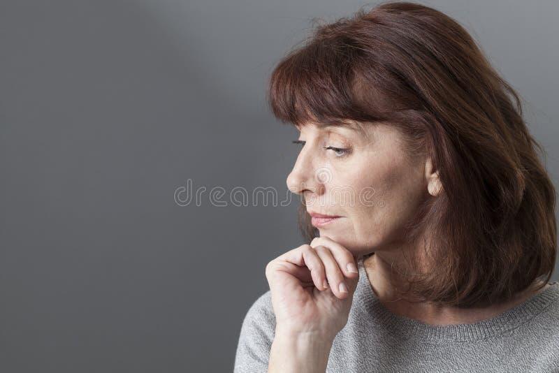 Meditar imaginativo da mulher 50s fotos de stock royalty free