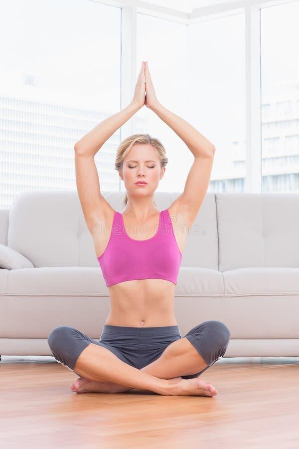 Meditar louro calmo na pose dos lótus com os braços aumentados imagem de stock royalty free