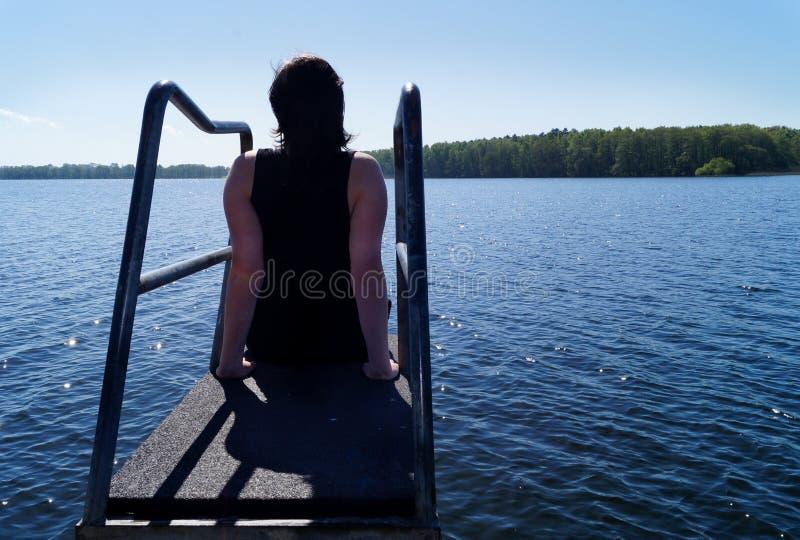 Meditar que se sienta de la mujer joven y disfrutar de las opiniones imagen de archivo