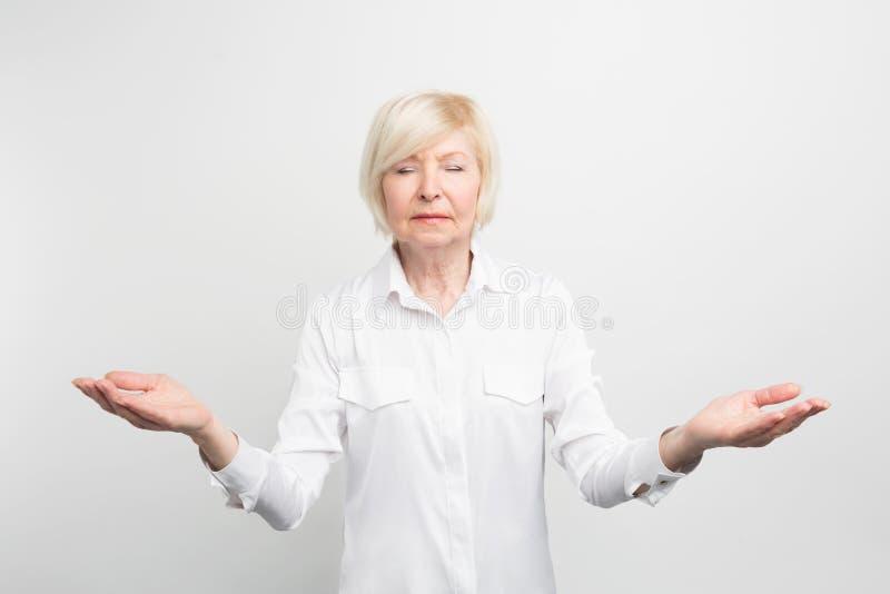 Meditar superior feliz da senhora Está procurando pela calma e está tentando encontrar-se Quer ser hapy em sua idade avançada foto de stock
