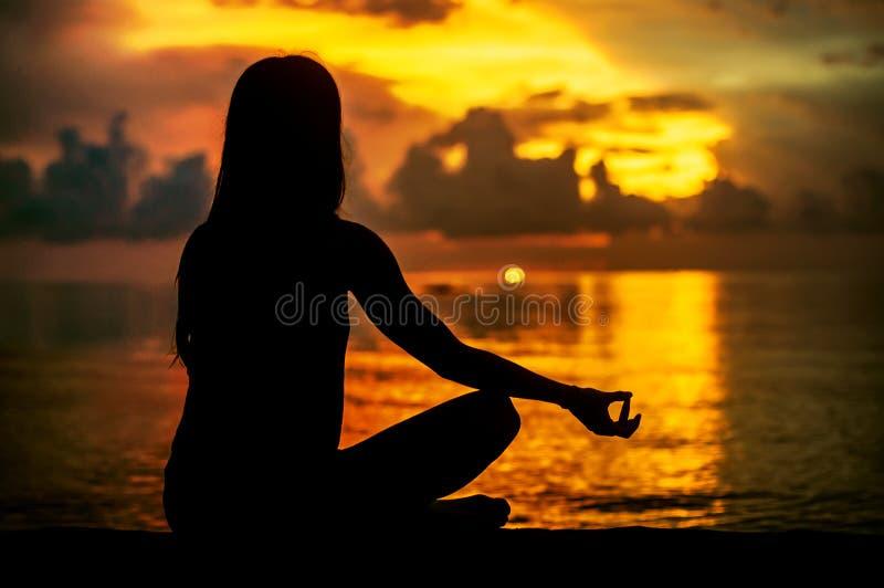 Meditare della donna, rilassantesi nella posa di yoga al tramonto, meditazione di zen fotografia stock libera da diritti