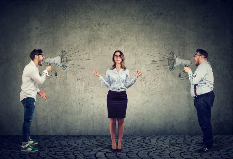 Meditare la donna di affari che non presta attenzione agli uomini arrabbiati che gridano lei in megafono immagine stock libera da diritti