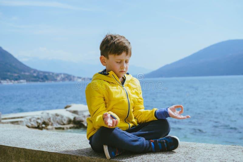 Meditare sveglio e ragazzo pacifico 7 anni in un rivestimento giallo immagini stock libere da diritti