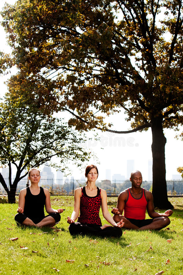 Meditate City. A group of people meditation in a city park stock photography