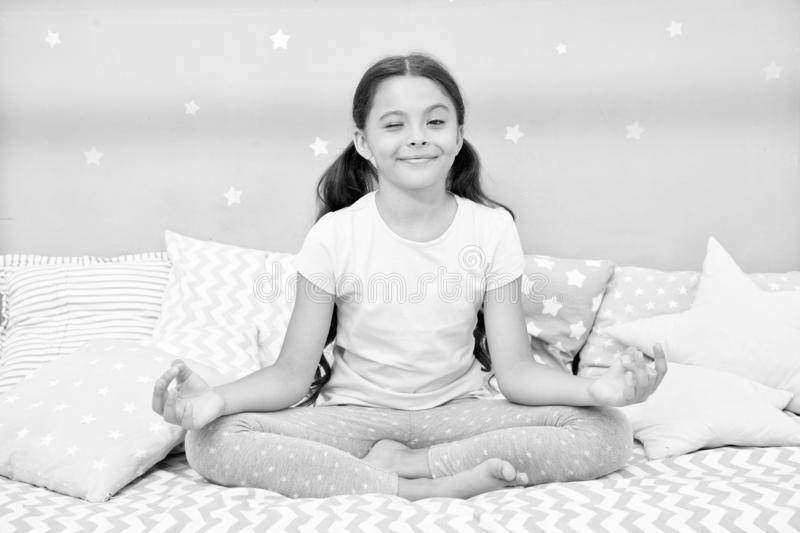 Meditate before go to bed. Girl child sit on bed in her bedroom. Kid prepare to go to bed. Pleasant time for evening stock images