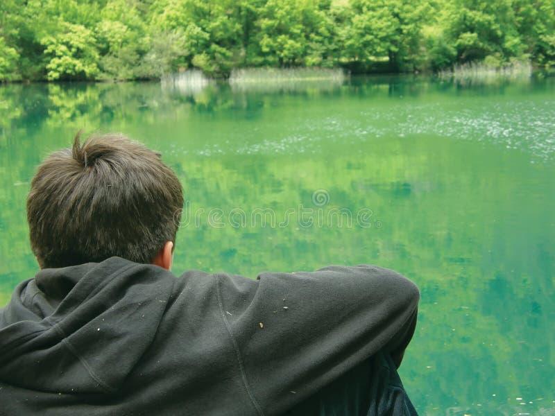 Meditate o menino e o rio fotografia de stock
