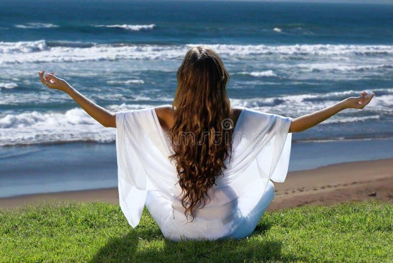 Meditatie van vrouw tegen oceaan royalty-vrije stock foto