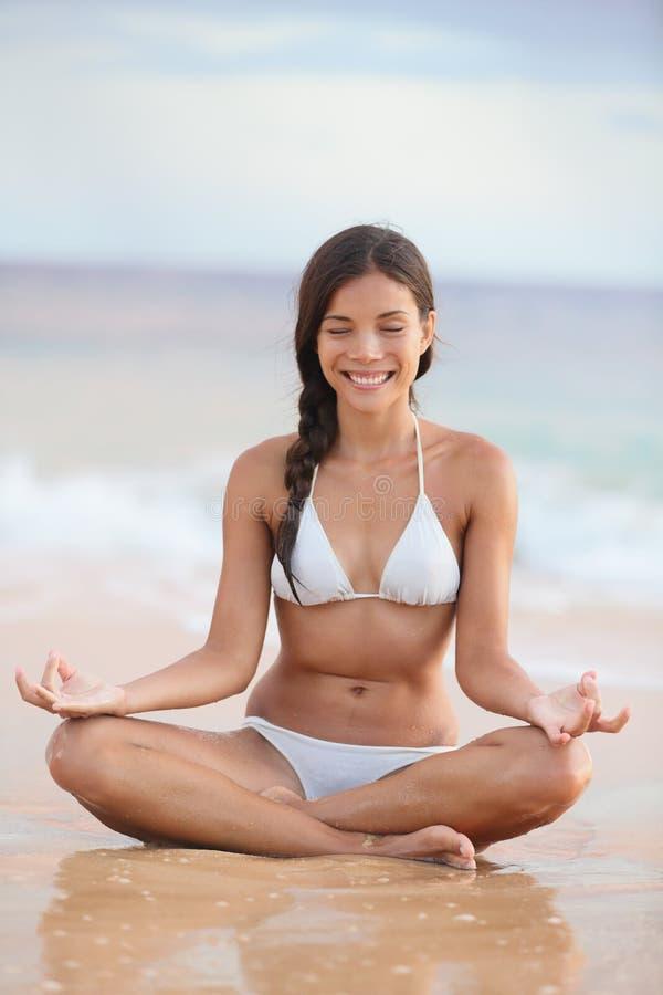 Meditatie - vrouw op strand die door oceaan mediteren stock afbeelding