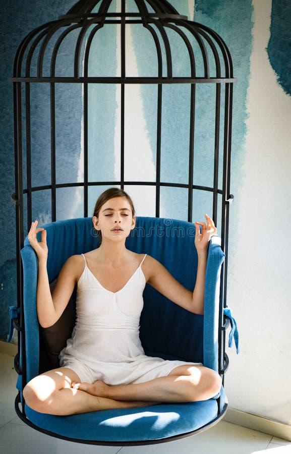 Meditatief en rustig Het leuke vrouwenconcentraat en mediteert als voorzitter De vrouw ontspant thuis in lotusbloempositie vrij royalty-vrije stock afbeeldingen