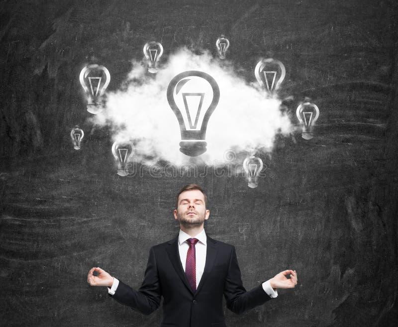 Meditatieve mens bij de wolk met gloeilampen als concept de nieuwe bedrijfsideeën Zwart schoolbord als achtergrond royalty-vrije stock foto's