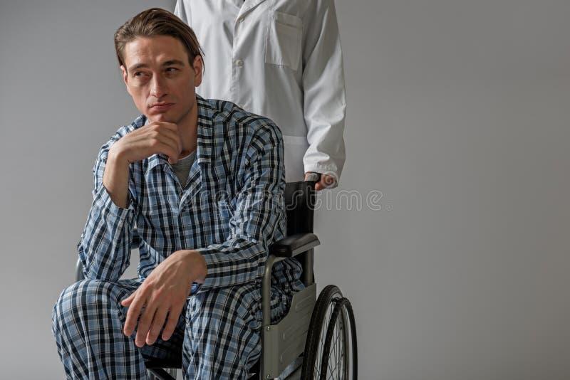 Meditatieve ongeldig vervoerd als voorzitter door verpleegster stock foto