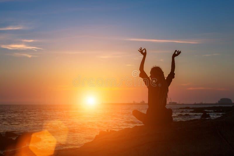 Meditatievrouw op de oceaan tijdens verbazende zonsondergang Yogasilhouet stock fotografie