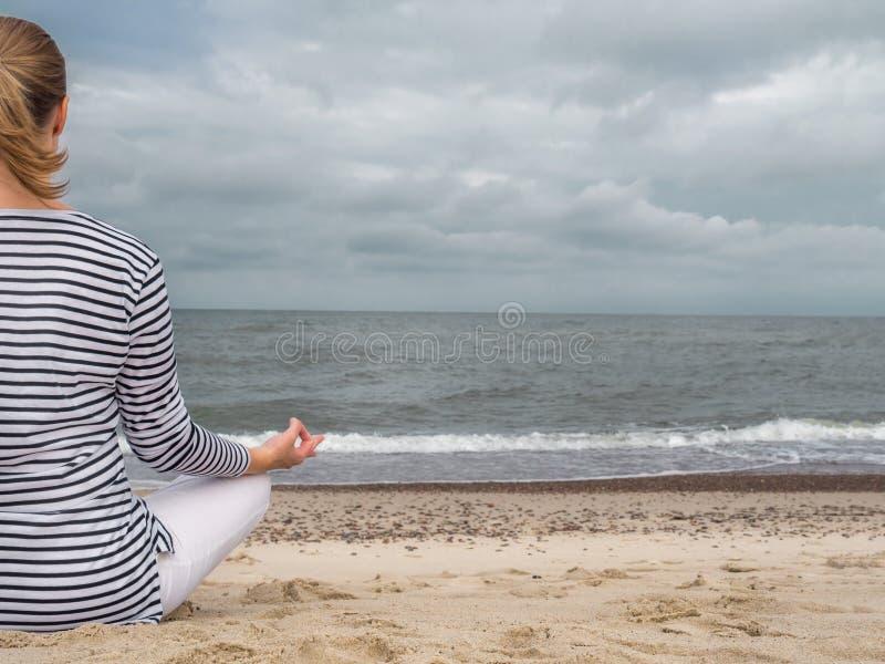 Meditating на пляже стоковые изображения rf