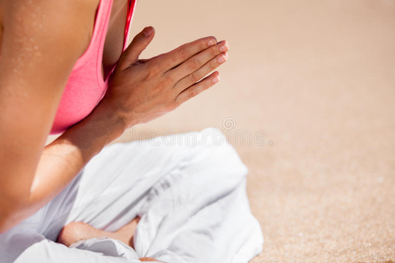 Meditating at the beach. Closeup of a woman body doing some yoga and meditation at the beach stock photography