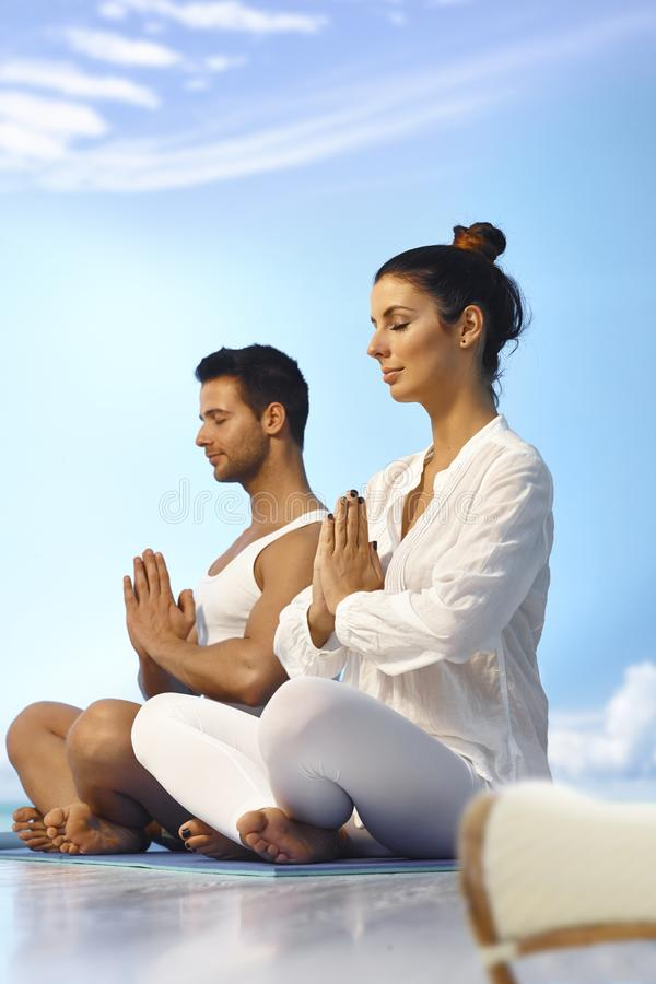 Meditating couple. Side view of meditating young people outdoors stock image