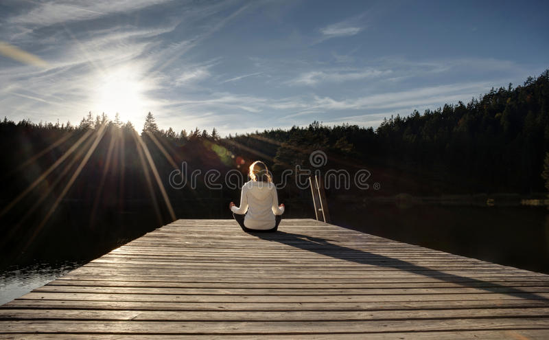 Meditating on a jetty at sunset. Young women meditating on a jetty at sunset stock photos