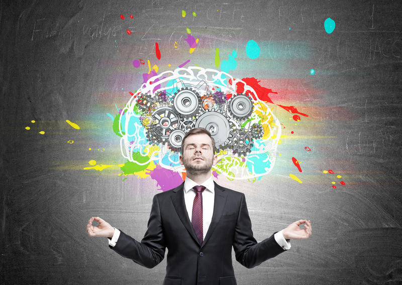 Meditating man and brain with cogs. Portrait of a meditating businessman wearing a black suit with a red tie and standing near a blackboard with a brain with stock photography