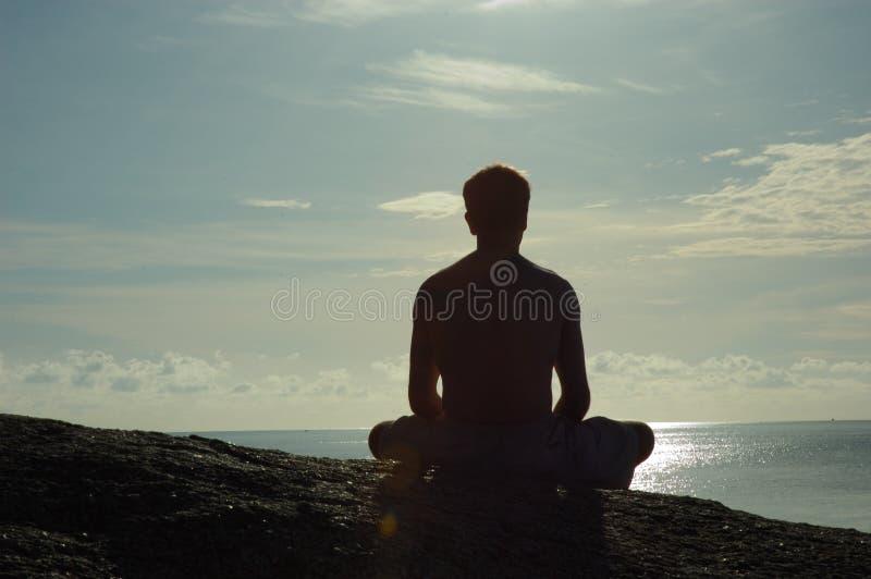 Meditating no oceano de negligência do nascer do sol foto de stock royalty free