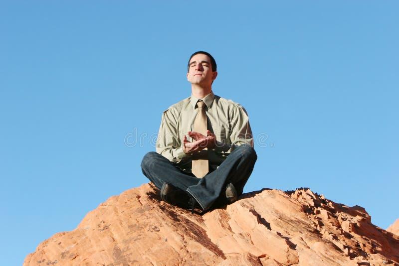 Meditating novo do homem de negócios/que relaxa foto de stock