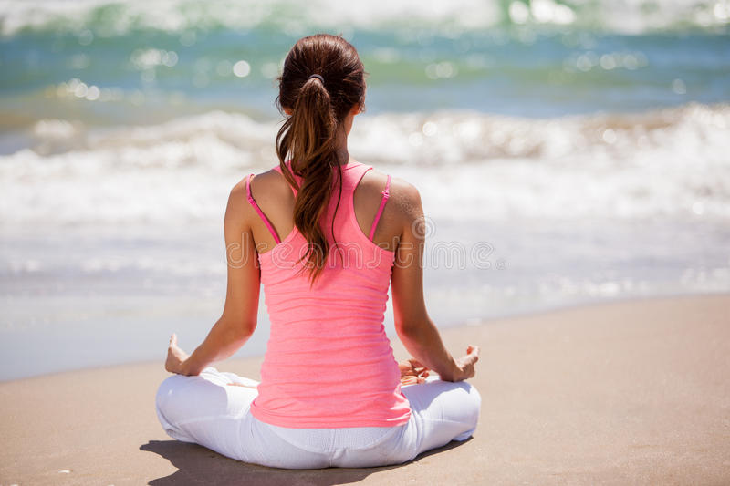 Meditating with the sound of waves. Young woman doing some meditation and yoga at the beach on a sunny day stock photos