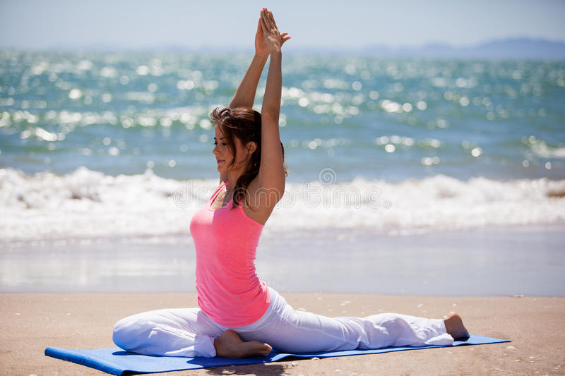 Meditating on a sunny day. Beautiful young woman meditating and doing some yoga at the beach stock photography