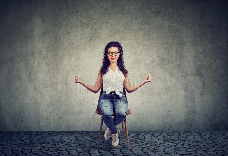Meditating woman on chair with eyes closed stock image