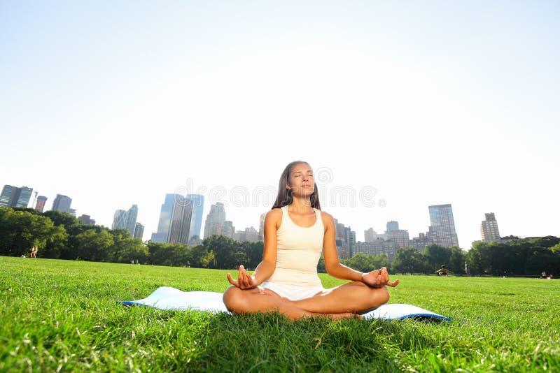 Meditating woman in meditation in New York park stock photos