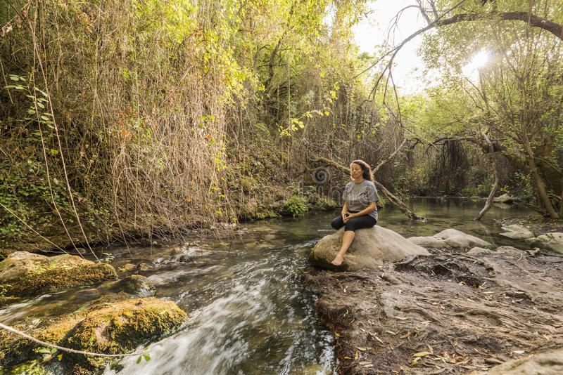 Meditating woman sitting on a rock at the edge of a river. Concept of lifestyle in nature royalty free stock image