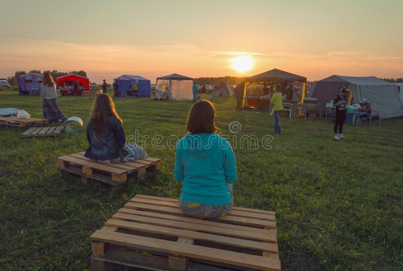 Meditating women at sunset of the day of solstice stock image