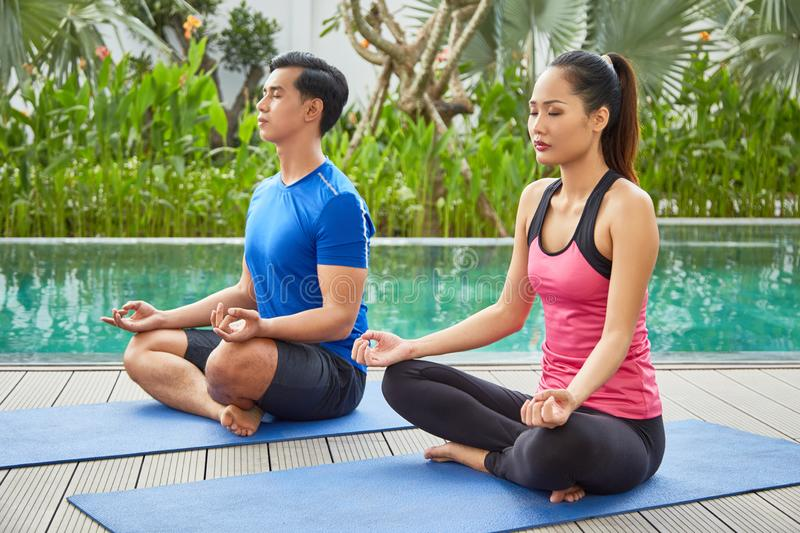 Meditating young couple royalty free stock images