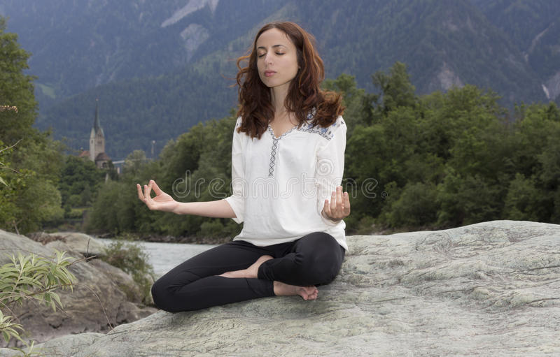 Meditating young woman outdoors in nature royalty free stock image