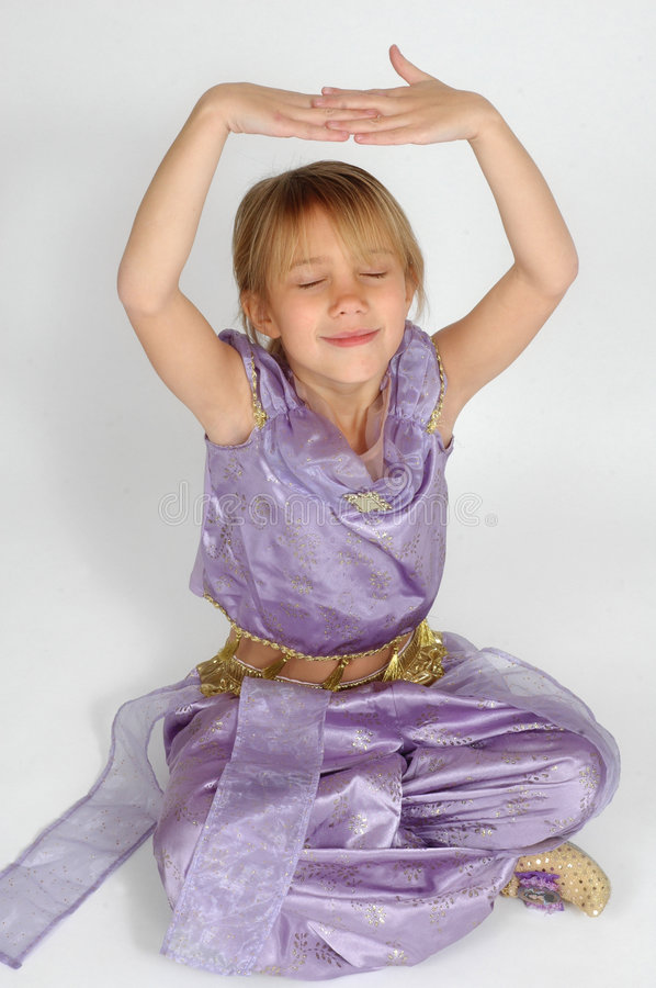 Meditation. A young girls sits on a white background with her arms up in the air and hands clasped together in a meditation mode. Child sitting with her legs stock photography