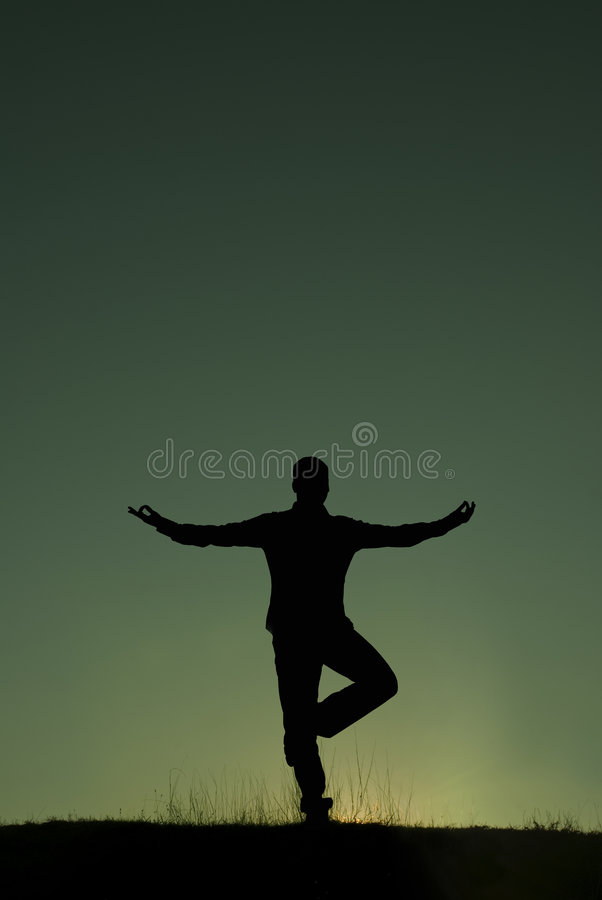 Meditation. Silhouette of a man meditating stock photo