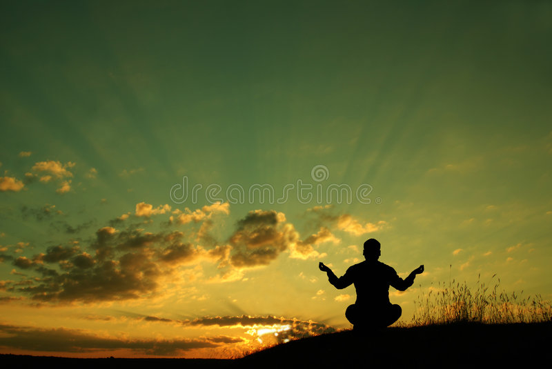 Meditation. Silhouette of a man meditating royalty free stock photo