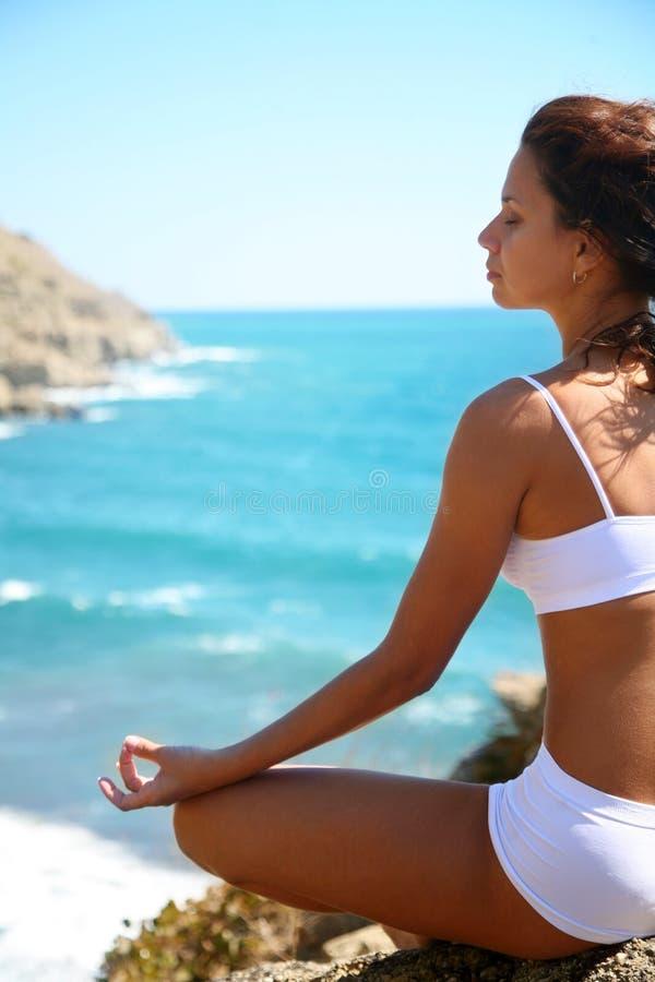 Meditation auf einer felsigen Küste stockfotografie